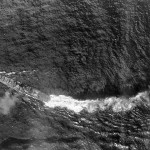 Chikuma under aerial attack during Battle off Samar in the Battle of Leyte Gulf, 25 October 1944. The ship's stern has been severely damaged by a torpedo hit, but the ship's outboard propellers are still keeping her somewhat moving.
