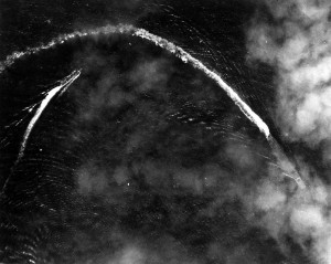 Akagi (right, partially obscured by clouds) takes evasive action during an aerial attack by US B-17s shortly after 08:00 on 4 June 1942. The trailing ship at left is probably the carrier's plane guard destroyer, Nowaki. The photograph was taken from one of the attacking B-17s.