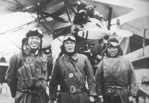 Ikuta, Kuroiwa, and Takeo pose in front of a Nakajima A1N2 Type 3 fighter aircraft.