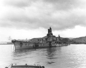 Japanese heavy cruiser Aoba sunk at Kure, Japan. She had been hit by air attacks on 24 and 28 July 1945, resulting in her loss. Note the large hole in her port side shell plating, forward, caused by a 500-pound bomb that penetrated her forecastle during the 24 July attack by U.S. Navy carrier aircraft.