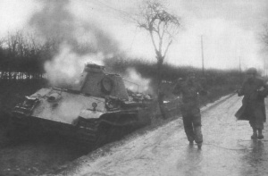 An American soldier escorts a German crewman from his wrecked Panther tank during the Battle of Elsenborn Ridge