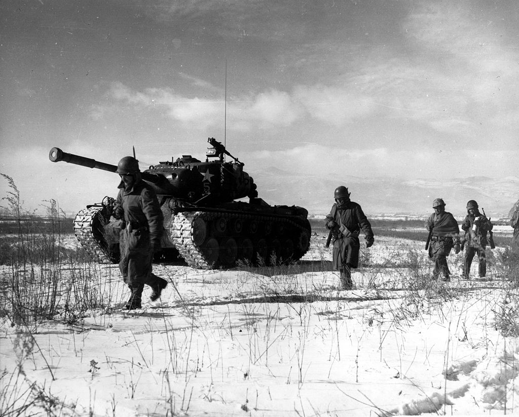 A column of troops and armor of the 1st Marine Division move through communist Chinese lines.