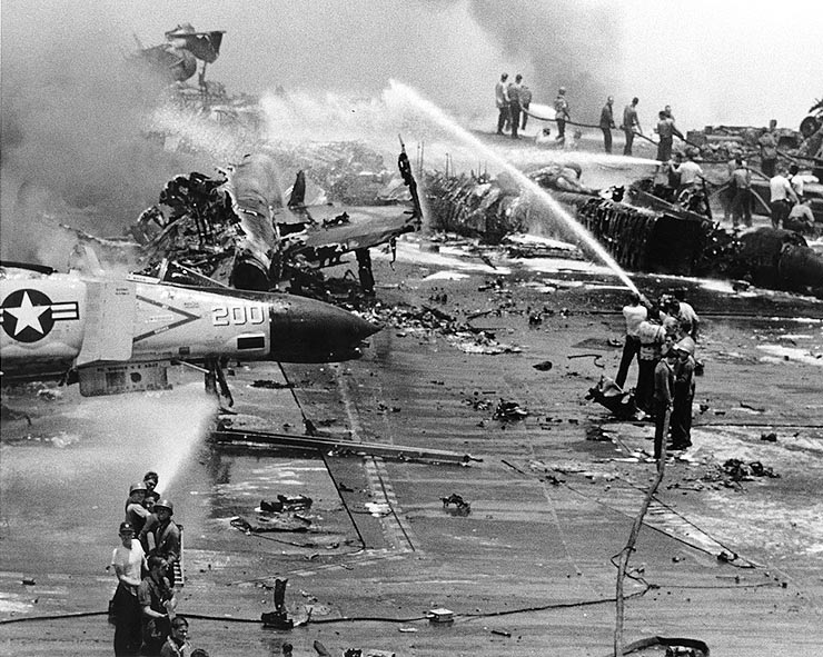 Crew members try to fight against the fires aboard USS Forrestal after the accident in 1967. This Image was released by the United States Navy with the ID USN 1124794. Public Domain.