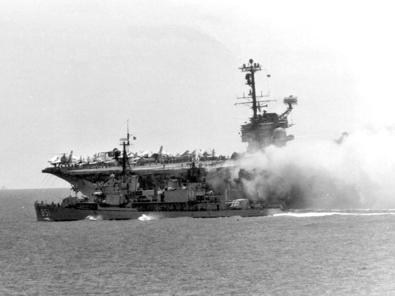 The destroyer USS  Rupertus (DD-851) assists the USS Forrestal  in flames.